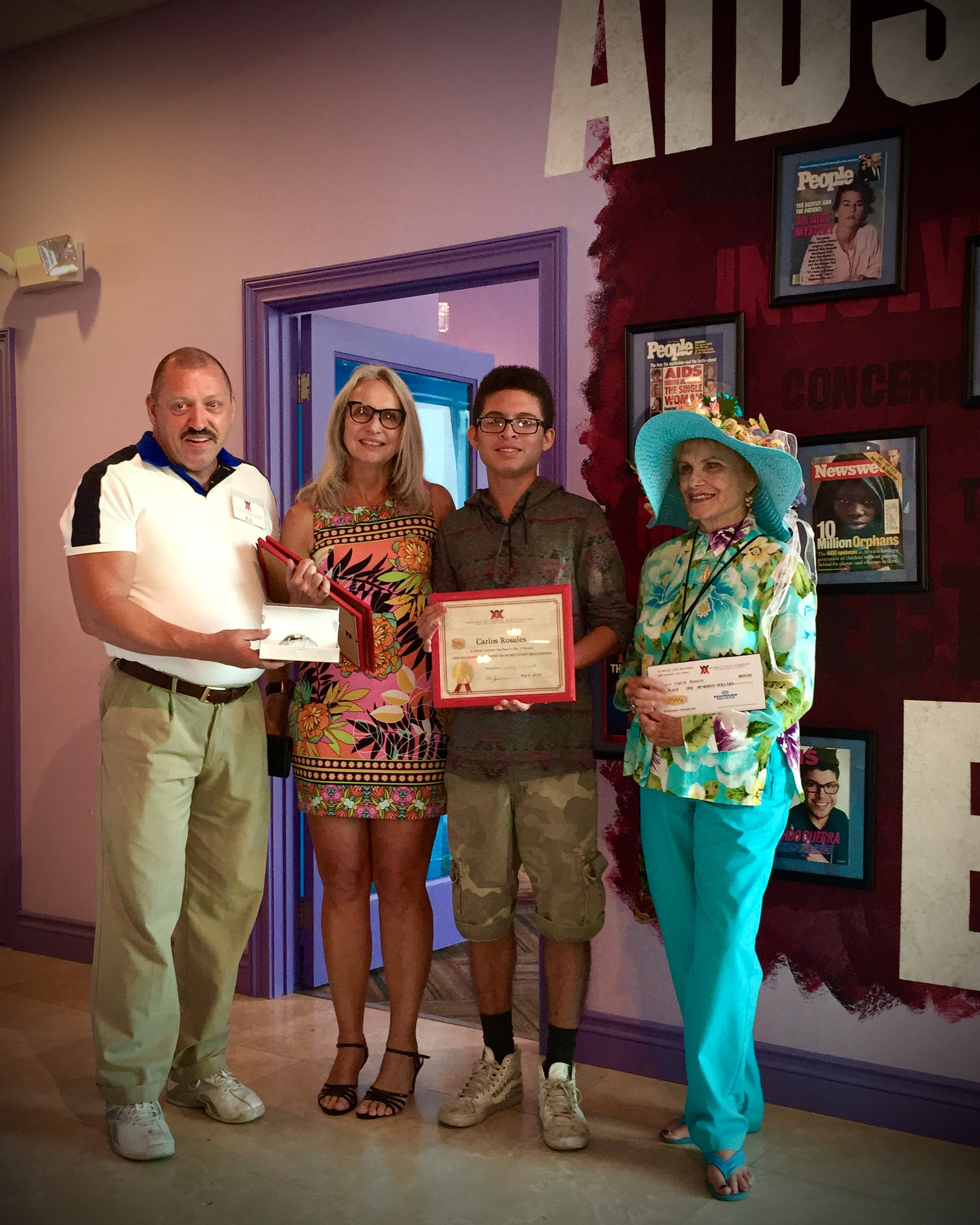Carlos Rosales, center, with his 2nd place award with Lynne Warrick and Jean Holcomb of the Lynne Warrick Institute which organized the AIDS art contest for Broward High School